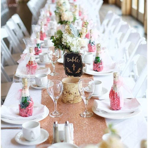 Long dining table decorated for wedding with miniature sparkling wine bottles wrapped in pink paper