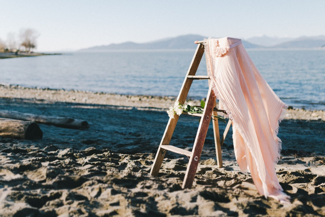 Pink fabric and white roses on wooden ladder on Vancouver beach
